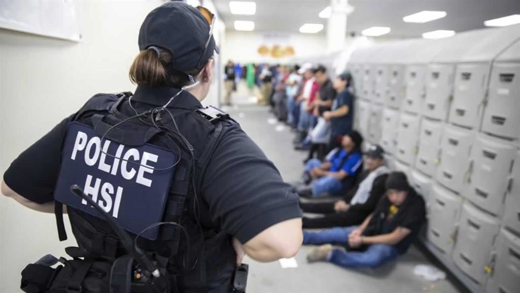 'A sad situation': An immigration agent watches over suspected illegal workers at a warehouse in Mississippi PICTURE: EPA