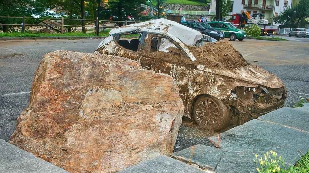 River of mud: A car is left battered and filthy after the landslide in Casargo PICTURE: REX