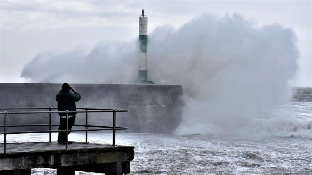 Stormy weather: A bystander risks high seas to take a photo of waves crashing at Aberystwyth, in Ceredigion PICTURE: SWNS