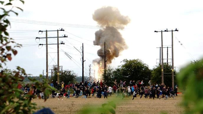 Terrifying: Spectators who had gathered to watch the towers fall flee after the pylon explodes in flames yesterday PICTURES: SWNS