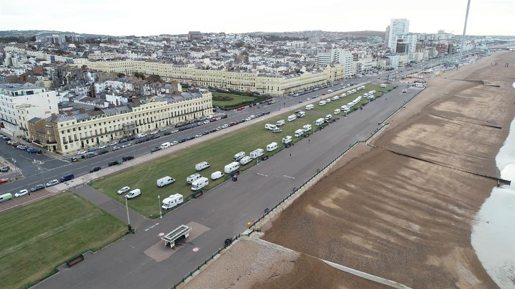 Site for sore eyes: Travellers' camp on Hove Lawns is opposite historic Brunswick Square, where flats sell for £800,000