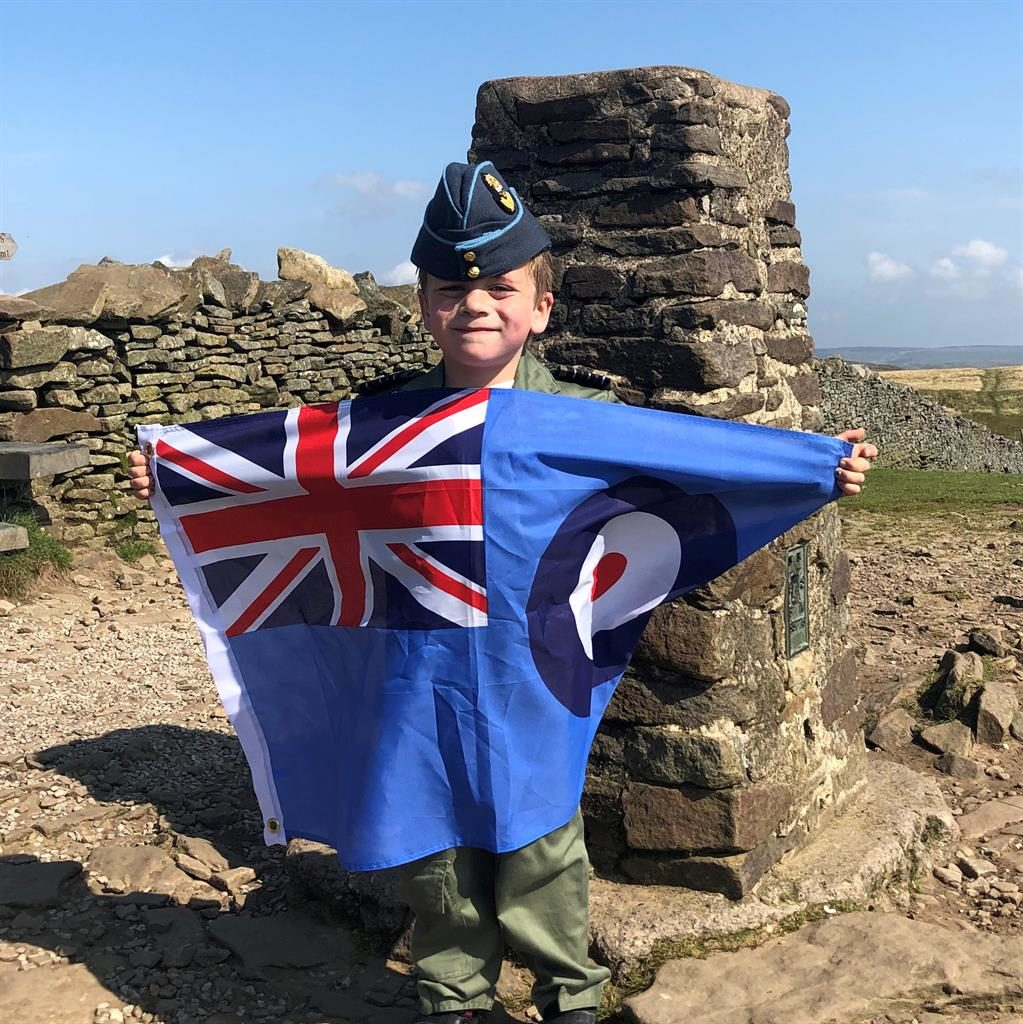 Flying the flag: Jacob reaches the top and unfurls an RAF standard PICTURES: SWNS