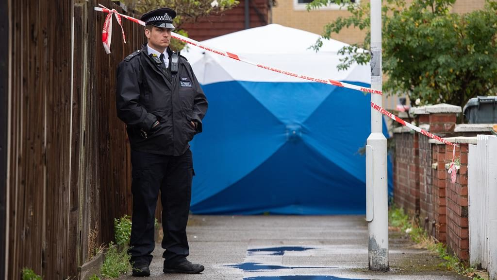 Murder inquiry: A policeman at the scene of the killing in Byford Close, Stratford PICTURE: PA