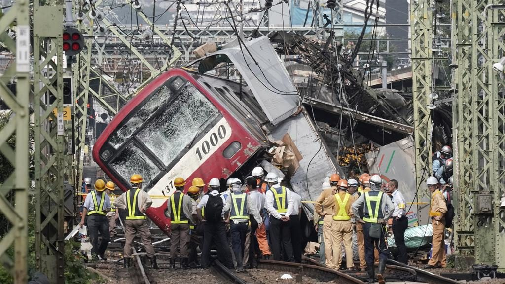 Train wreck: Rescue workers at the scene of the crash PICTURE: KIMIMASA MAYAMA/EPA