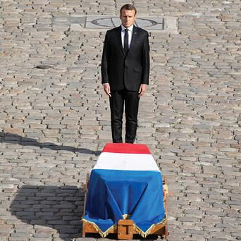 Paying his respects: Emmanuel Macron stands in front of Mr Chirac's coffin, draped in the national flag PICTURES: REX/EPA