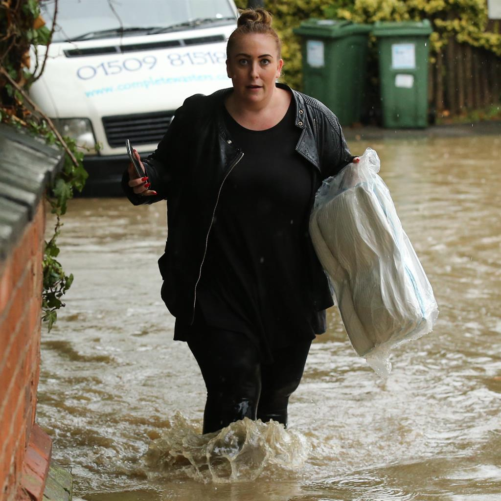 Waders on: A woman carries empty sandbags through Sileby, Leicestershire PICTURE: SWNS