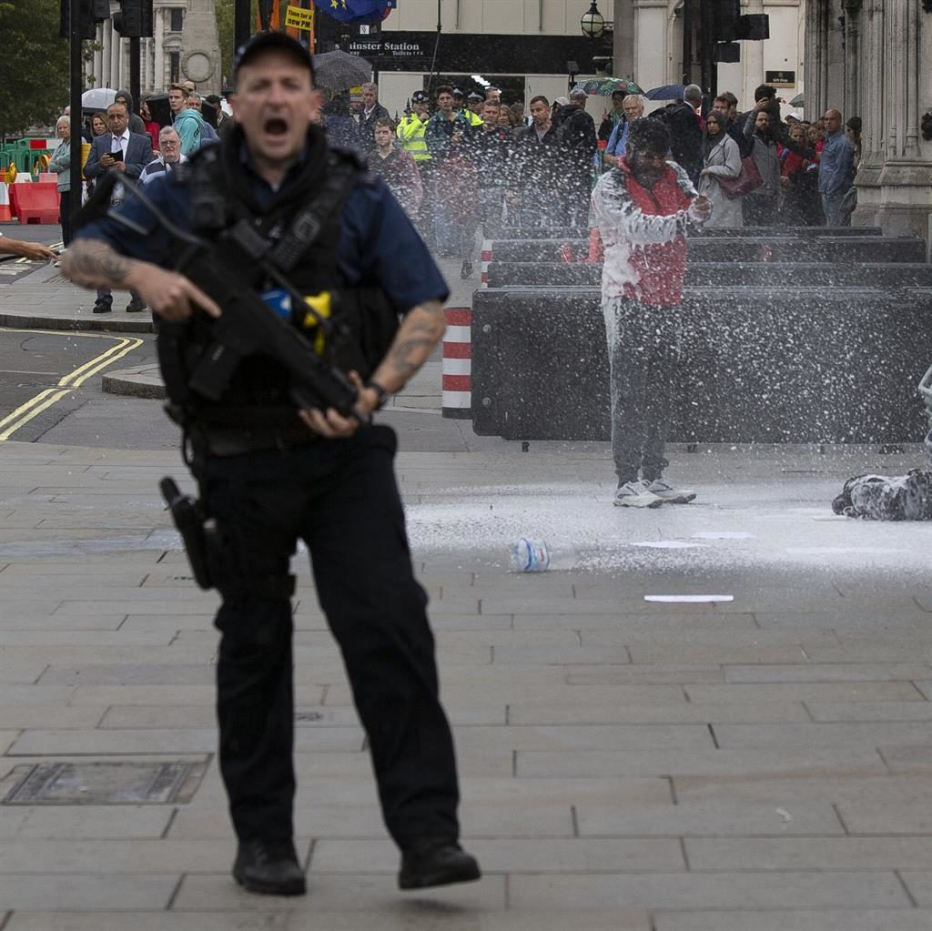 Flashpoint: A policeman hoses the man down as an armed officer warns people to get back