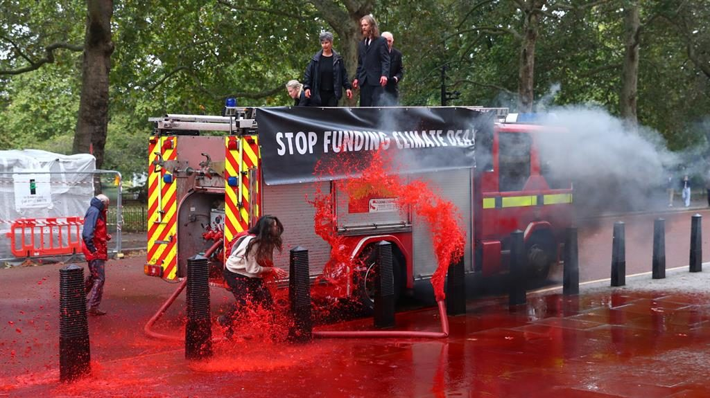 Demon-spray-tion: Protesters turn on the hose (below) but quickly lose control, covering themselves and the street in dyed water PICTURES: REUTERS