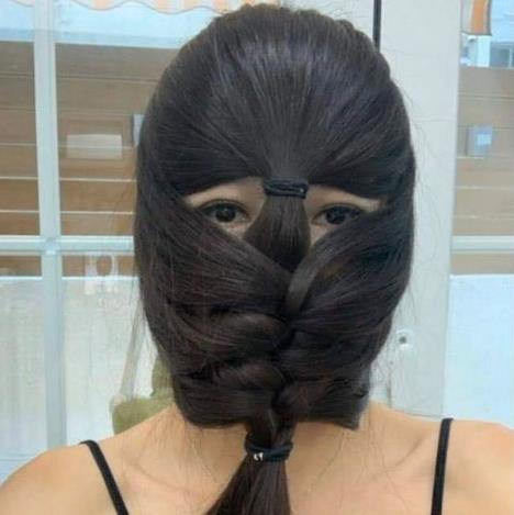 Plaits how you do it: A woman uses her hair to cover her face PICTURE: RAY KWONG