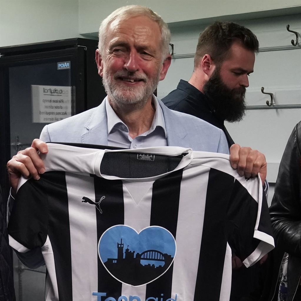 Pledge: Mr Corbyn with charity shirt PICTURE: PA