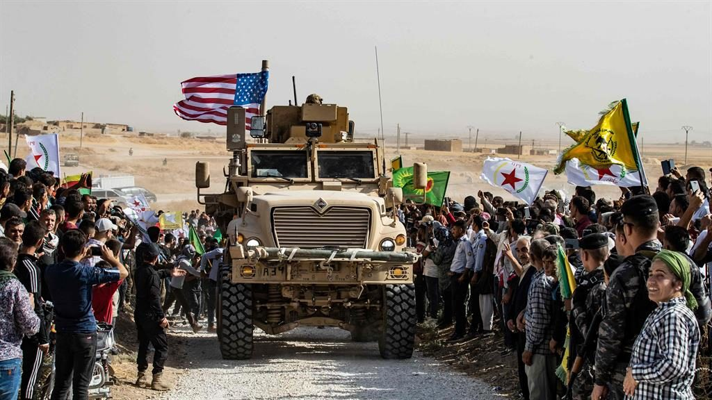 Backlash: Kurds standing by a US armoured vehicle in Syria to protest Turkish threats PICTURE: AFP