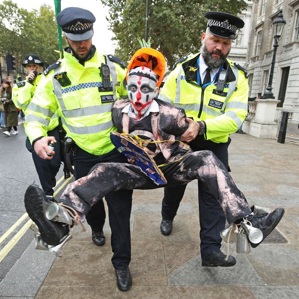 Fears of a clown: Police carry away a protester during the Extinction Rebellion demonstration in Westminster yesterday PICTURE: PA