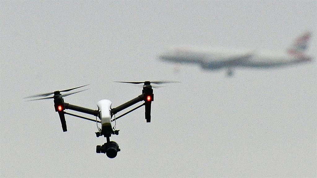 Too close for comfort: A drone flies with a plane visible behind it PICTURE: PA