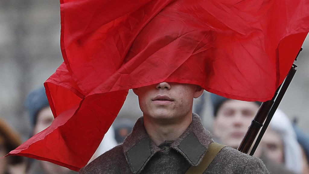 Wind of change: A gust pushes a Soviet flag over the face of a soldier in Red Square