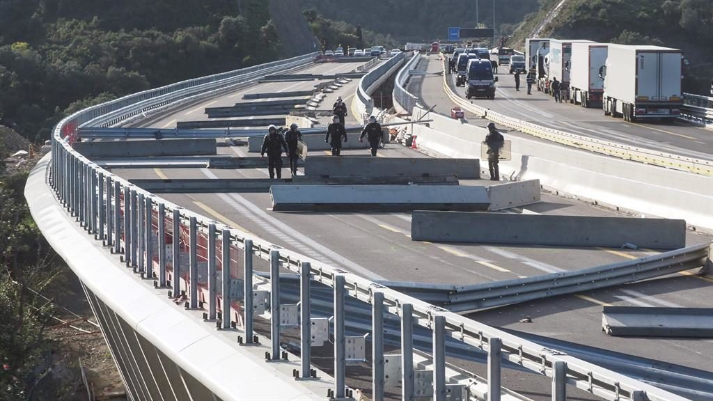 Hazards: Riot police inspect debris used to stop traffic on the A9-AP7 motorway  linking France and Spain PICTURE: GETTY