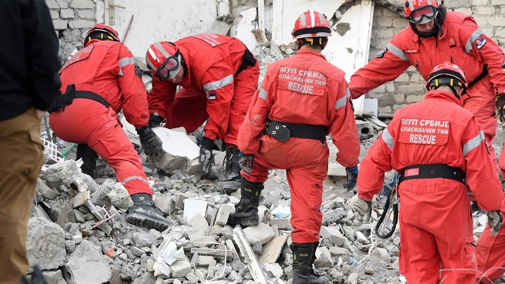 Multi-national effort: Rescue workers from Serbia lift blocks of rubble in Thumane