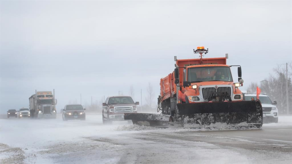 Clearing: A snowplough removes snow and ice from a highway in Iowa after storms disrupted roads and flights on one of the busiest days for US travel PICTURE: GETTY