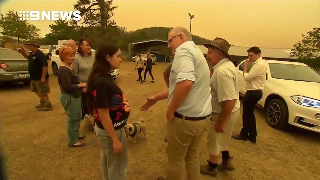Unwelcome: A woman refuses to shake the hand of Australian prime minister Scott Morrison in Cobargo, NSW, before he cut short his visit (below) PICTURES: NINE NEWS