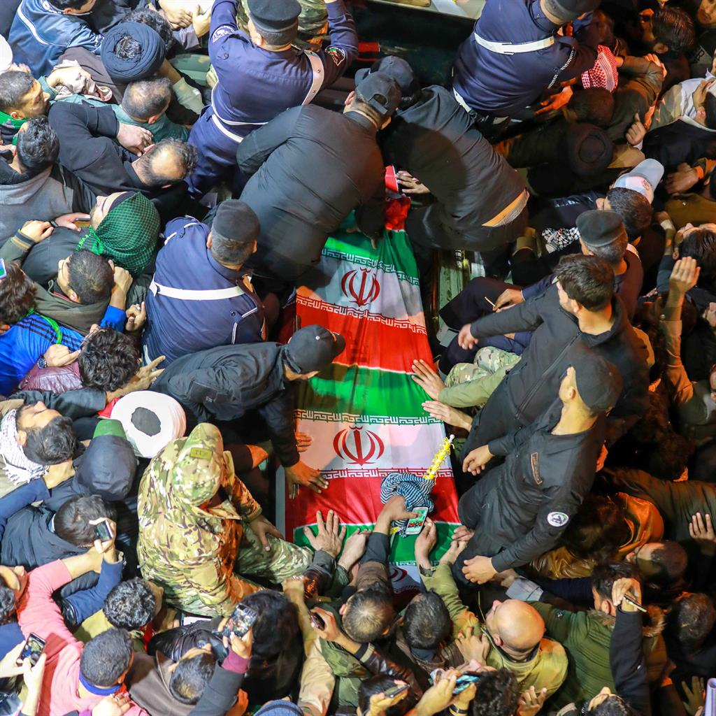 National outpouring: Iranians gather around the flag-draped coffin of Gen Qasem Soleimani PICTURE: EPA