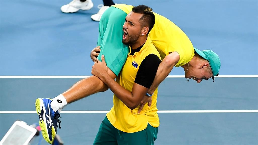 Up there: Nick Kyrgios carries teammate Alex de Minaur after winning their men's doubles match against Jamie Murray and Joe Salisbury (below) PICTURE: GETTY