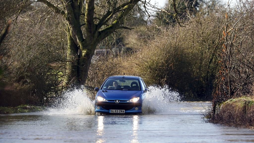 Ploughing through: Vehicles negotiate the flooded B4069 road at Christian Malford in Wiltshire after the river Avon burst its banks PICTURES: PA