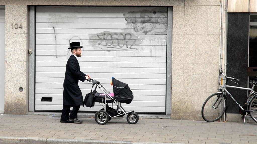 .Stroll on: A Jewish father pushing his baby through Antwerp and, below, Margot