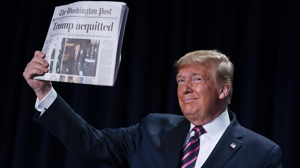 Triumphant: Donald Trump holds up a copy of the Washington Post PICTURE: AP