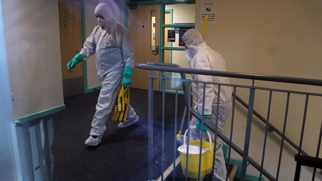 Proceed with caution: Workers in head-to-toe protective gear clean County Oak Medical Centre in Brighton PICTURE: EPA