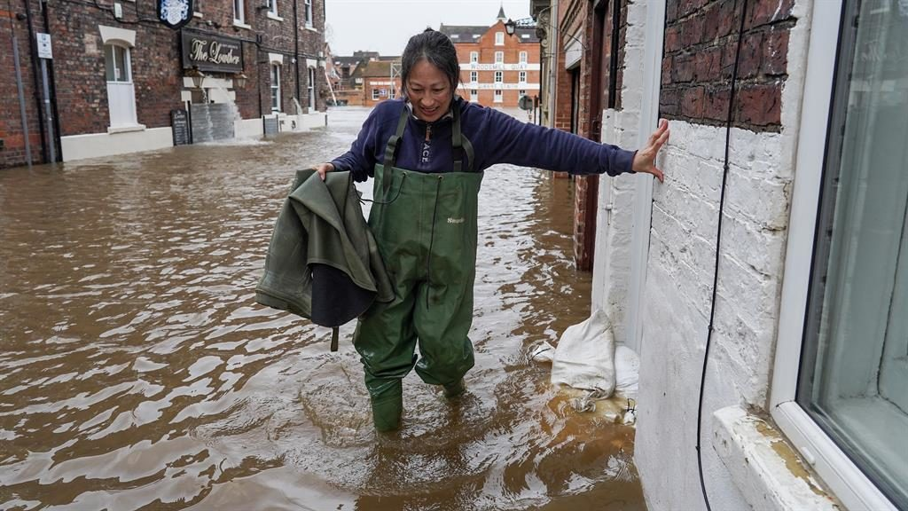 Treading water: A woman wades through floods after the river Ouse breached its banks in York PICTURE: GETTY/PA