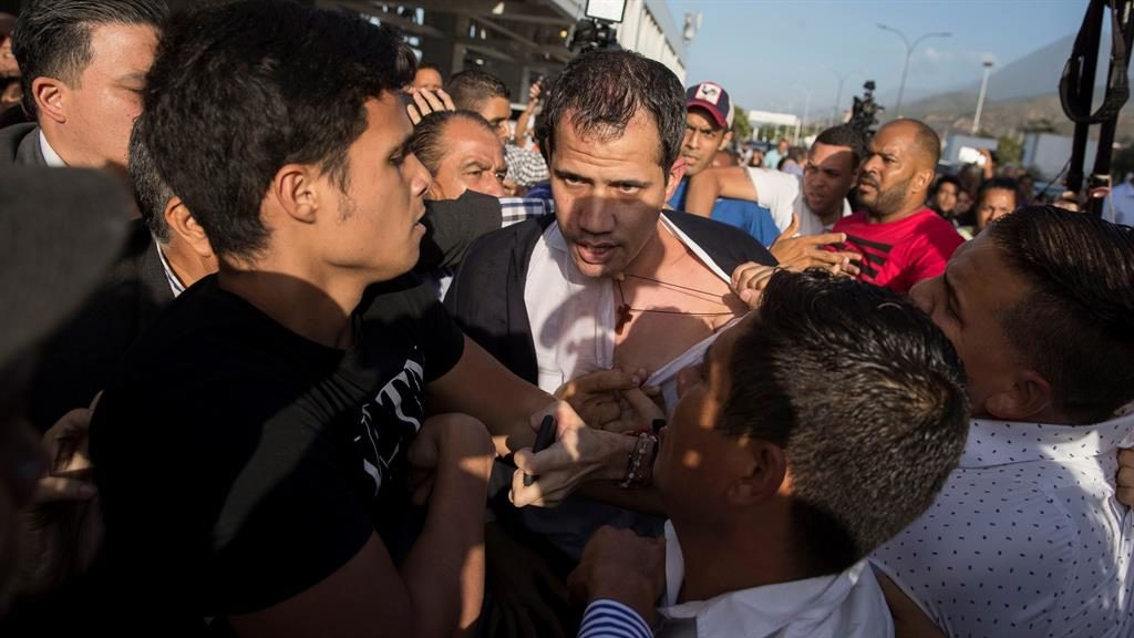 Scuffles: Juan Guaido is grabbed by Maduro supporters as he arrives in Caracas PICTURE: EPA