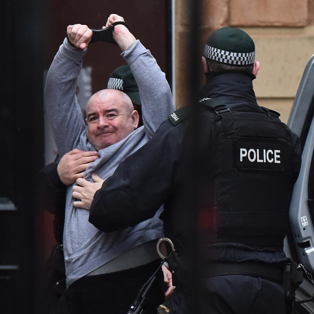 Show of defiance: Police lead Paul McIntyre into court PICTURE: GETTY