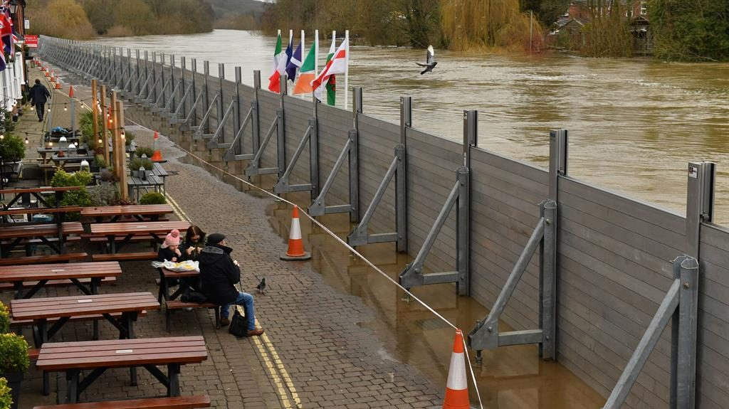 All bite for now: A family have lunch as barriers hold back water from above their heads in Bewdley, Worcestershire PICTURE: PA