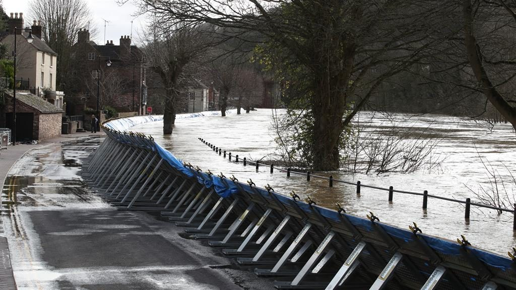 Warning: Temporary flood barriers fight the rising water level in Ironbridge, Shropshire. (Below) homes in the town were flooded as the Severn swelled PICTURES: PA
