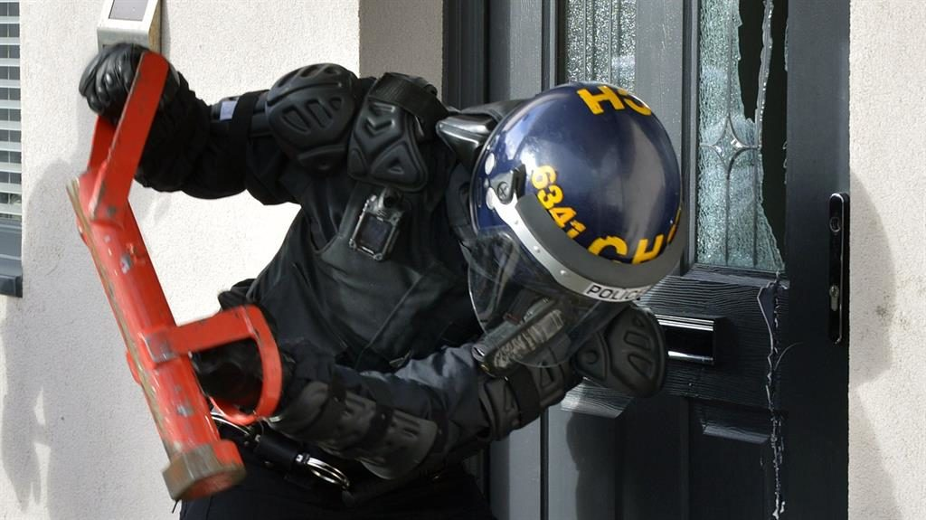 Hard knock: A police officer breaks into a house PICTURES: MERSEYSIDE POLICE