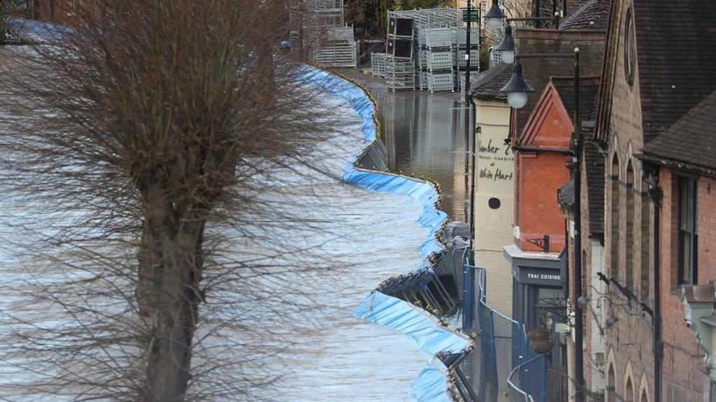 Risk to life: Water laps over temporary flood barriers in the town of Ironbridge in Shropshire PICTURE: PA