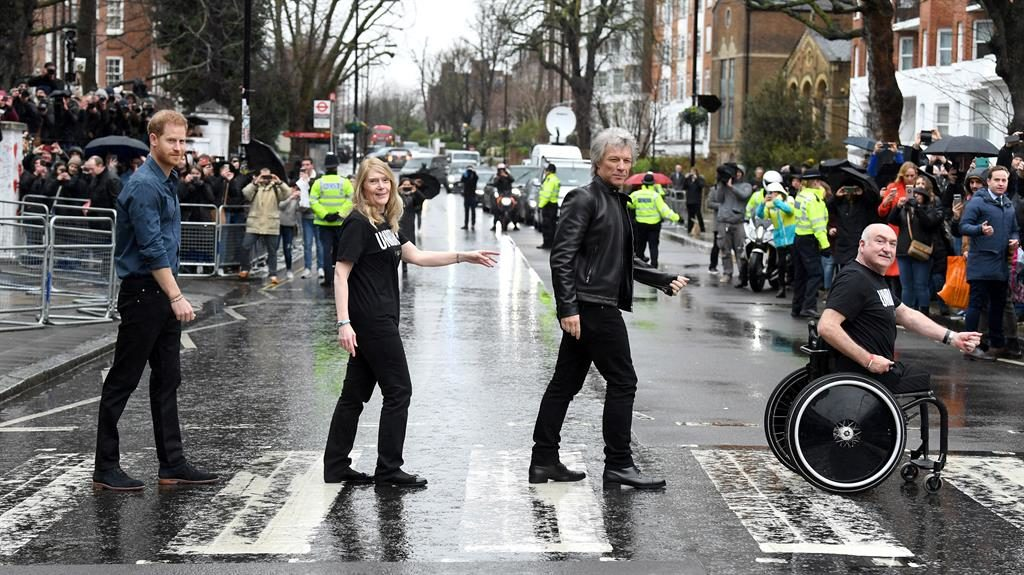 Come together: Harry, Jon Bon Jovi and members of the Invictus Games Choir on the zebra crossing outside the studios PICTURES: GETTY