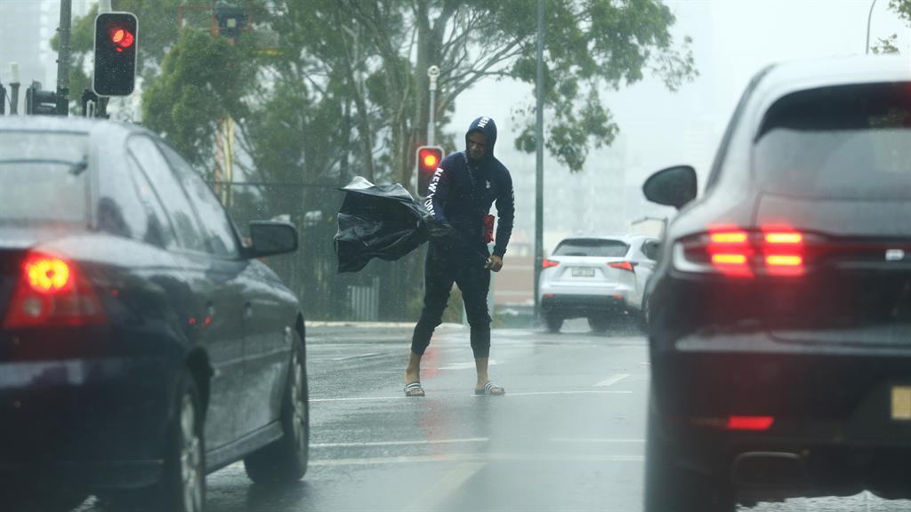 Wet walk A man struggles to cross road