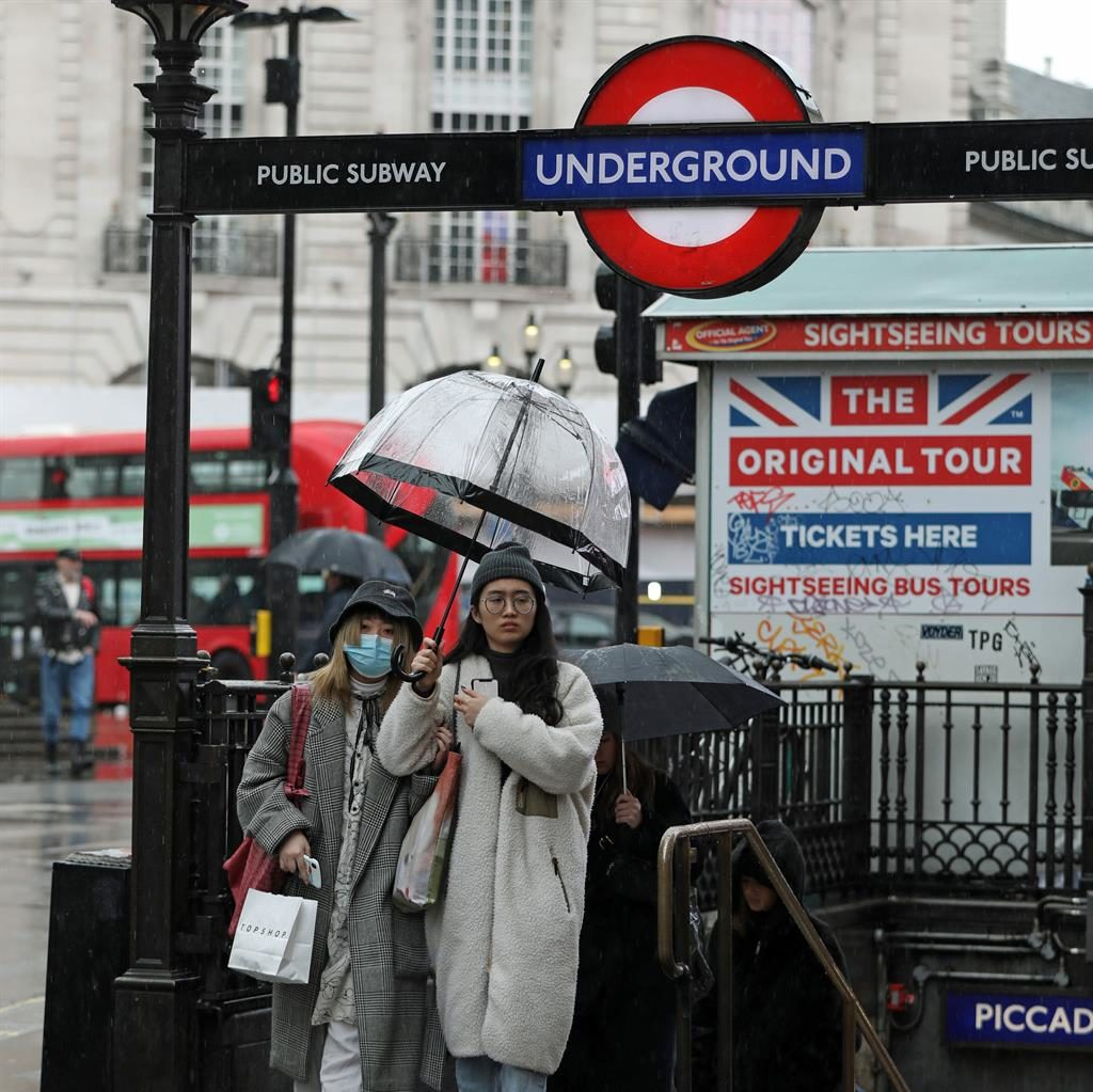 Precautions: A woman wearing a face mask (left) leaving Piccadilly Circus tube PICTURES: PA