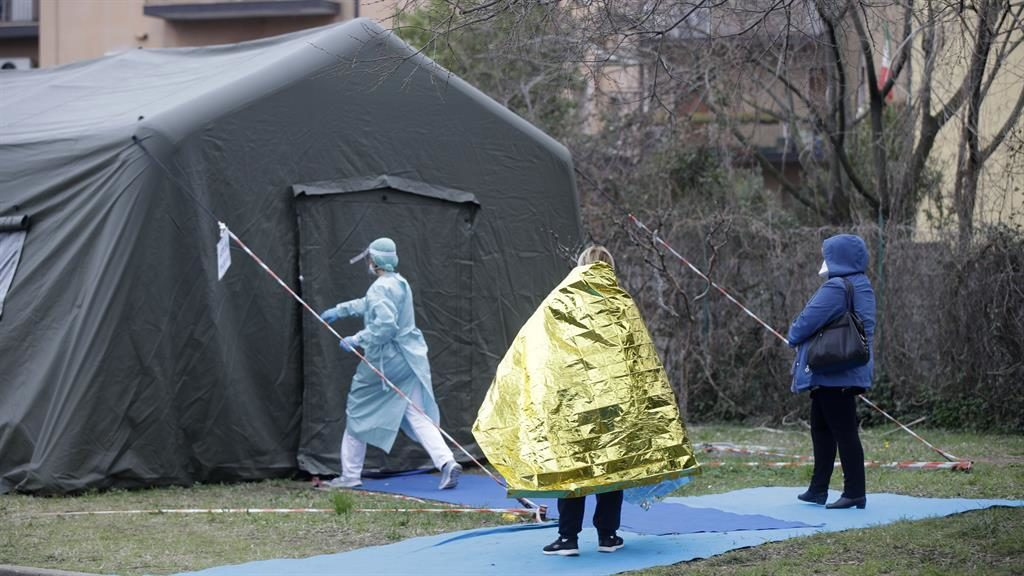 Lockdown: A woman waits to enter an isolation tent in Brescia, Italy PICTURE: AP