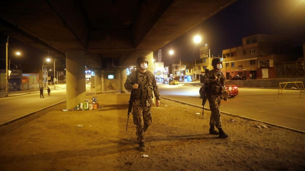 Lockdown: Soldiers patrol a street during a nighttime curfew in Lima, Peru