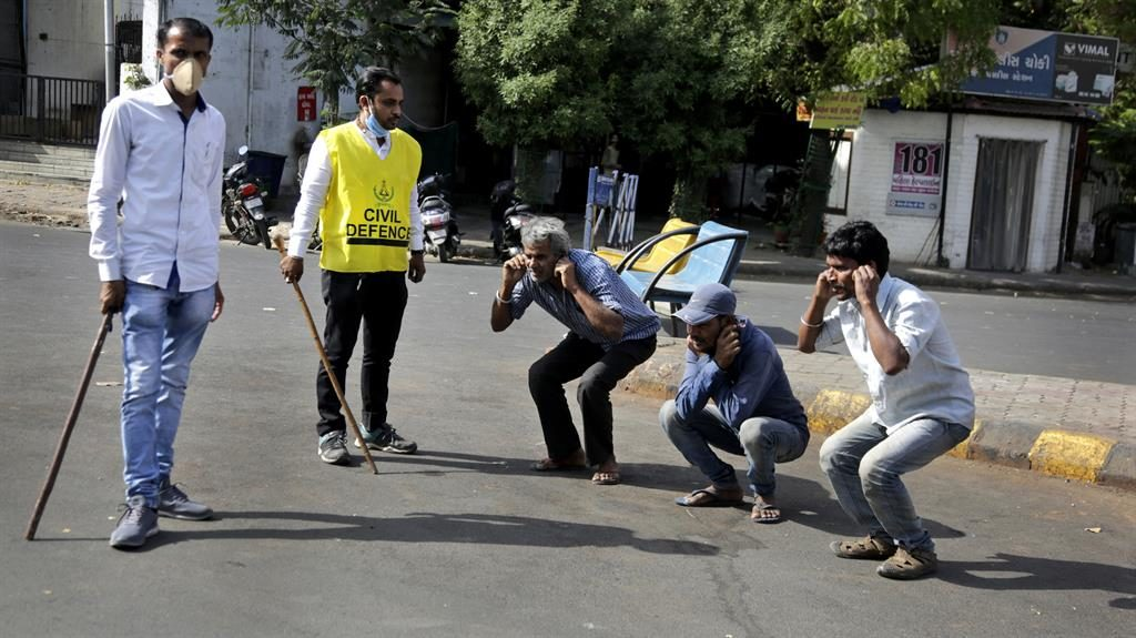 Punishing: Police make men perform squats after spotting them out in Ahmedabad PICTURE: AP