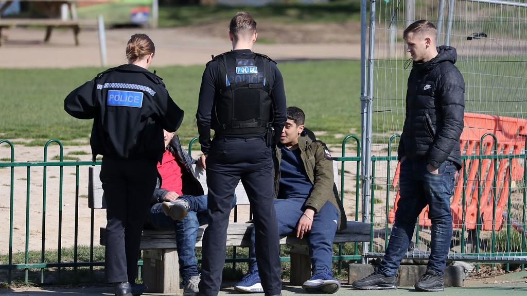 Three's a crowd: A group of people are spoken to by Kent Police before being told to leave a  play area in Maidstone PICTURES: PA/NNP