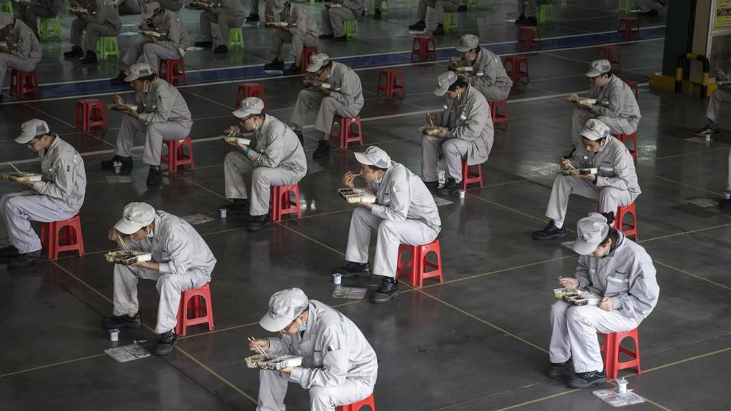 Employees eat their lunch while staying two metres away from each other at a car plant in Wuhan, Hubei province, China PICTURE: GETTY