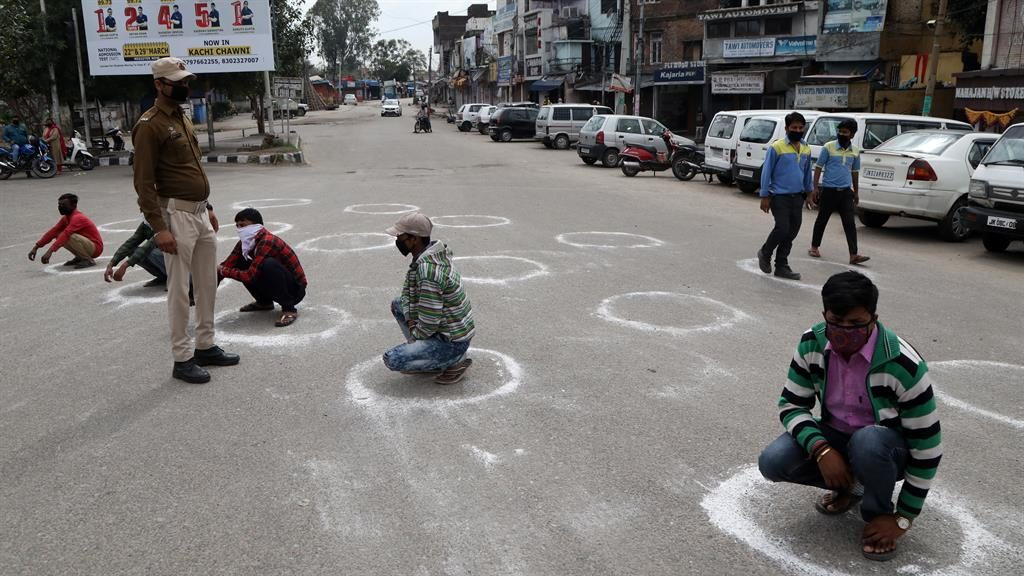 Punishment: Police make rule-breakers squat in circles in Jammu PICTURE: JAIPAL SINGH/EPA