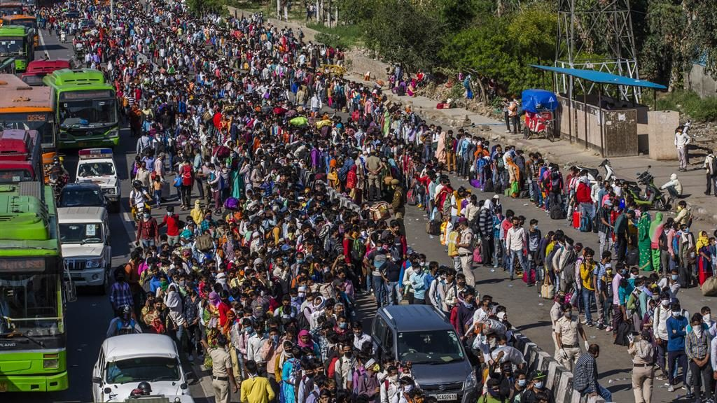 Get me out of here: Thousands of migrant workers queue to board buses to take them from New Delhi to their homes elsewhere PICTURE: EPA