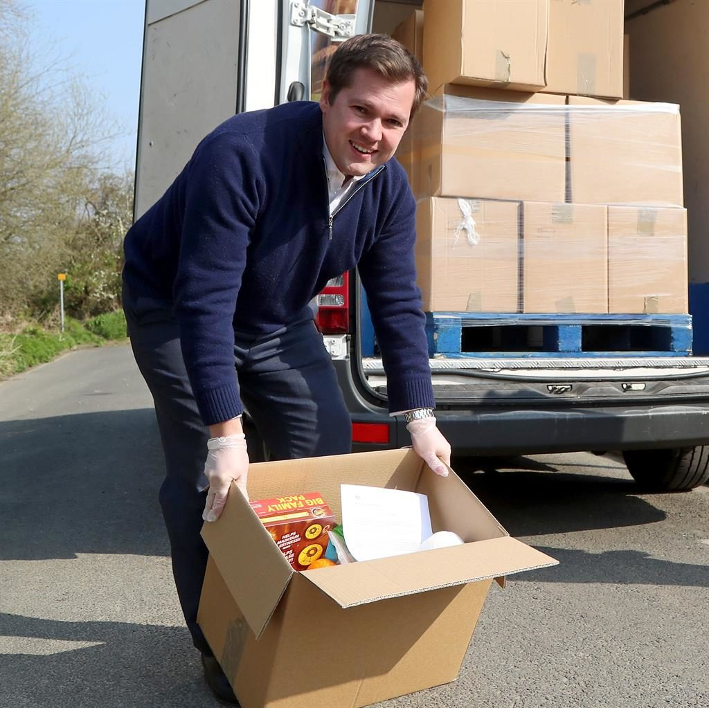 Helping hand: Robert Jenrick helps with deliveries in Kent PICTURES: GARETH FULLER/PA