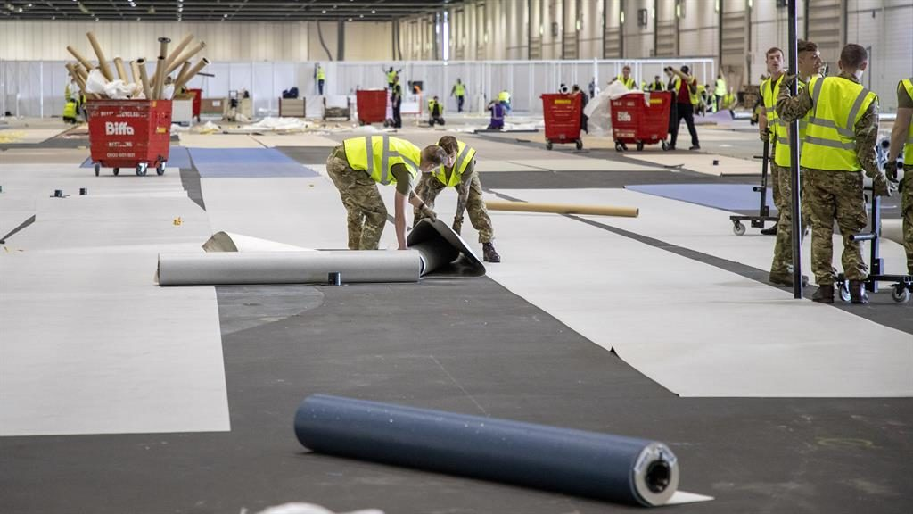 Fit for action: Soldiers lay out carpet at ExCel London PICTURE: UK MOD