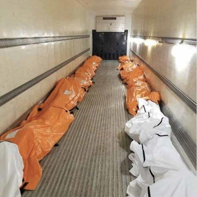 Mounting death toll: Body bags line a refrigerated lorry container outside a hospital in Manhattan