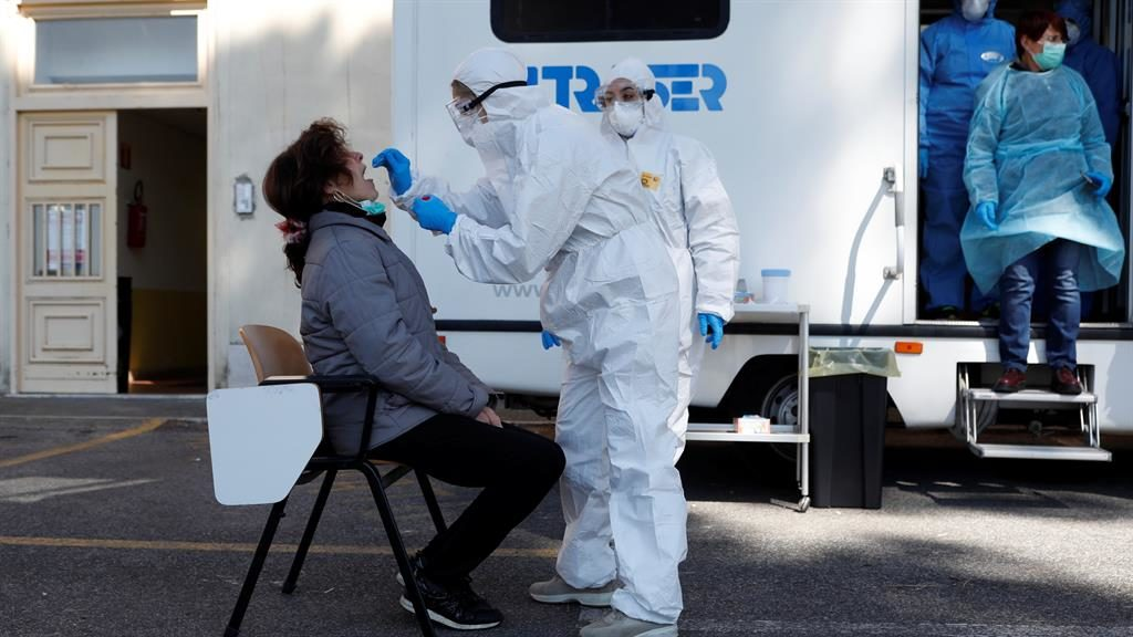 Swabbed in street: A woman is tested by medical staff in Rome PICTURE: REUTERS