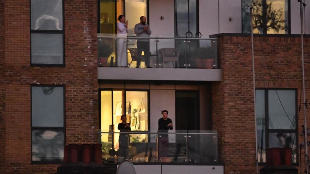 Touch of glass: Supporters applauding from their balconies in Kensal Green, London, last night